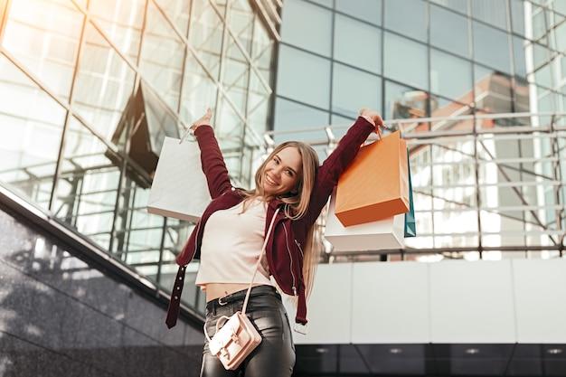 Van onderen inhoud jonge stijlvolle vrouwelijke shopaholic in trendy outfit boodschappentassen in opgeheven handen houden en kijken, terwijl staande tegen moderne glazen winkelcentrum voortbouwend op stedelijke straat