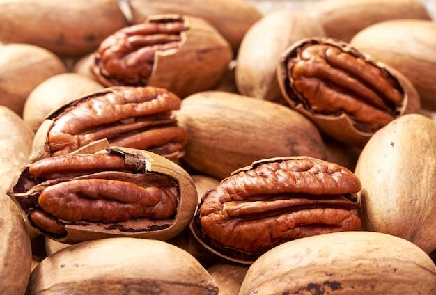 Van pecannootnoten close-up als achtergrond, gezond voedsel. smakelijke pecannoot als achtergrond, als pecannoottextuur. plat leggen.