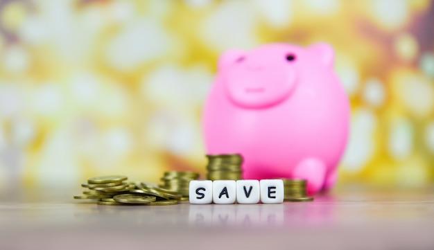 Van sparen geld munt stapel groeiende bedrijf of investering of beurs, sparen geld en spaarvarken op de houten tafel bokeh