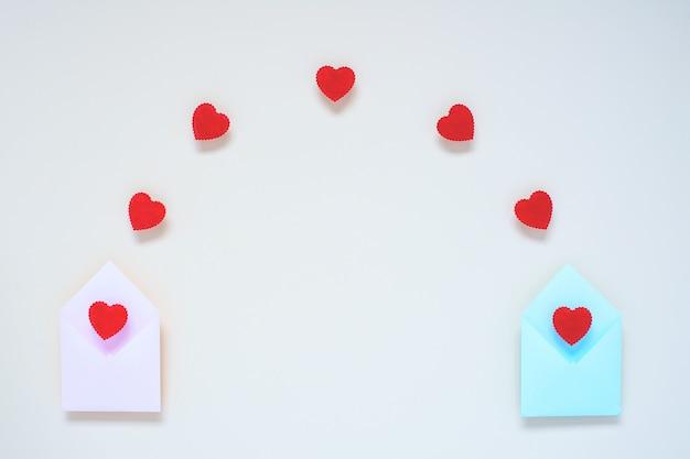 Van twee enveloppen vliegen rode harten.