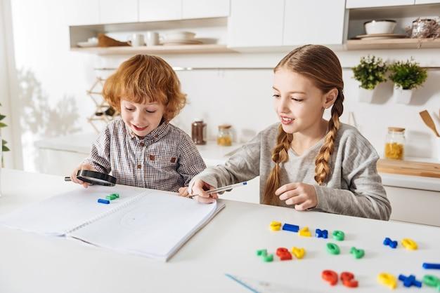 Van wiskunde houden. hardwerkende intelligente jongedame die haar wiskundige opdracht doet om de formules op te schrijven terwijl haar kleine broertje gefascineerd is door een reeks kleurrijke getallen