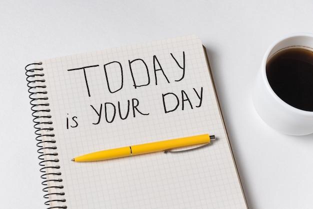 Vandaag is uw dag motivatiebericht. kladblok, pen en kopje koffie.