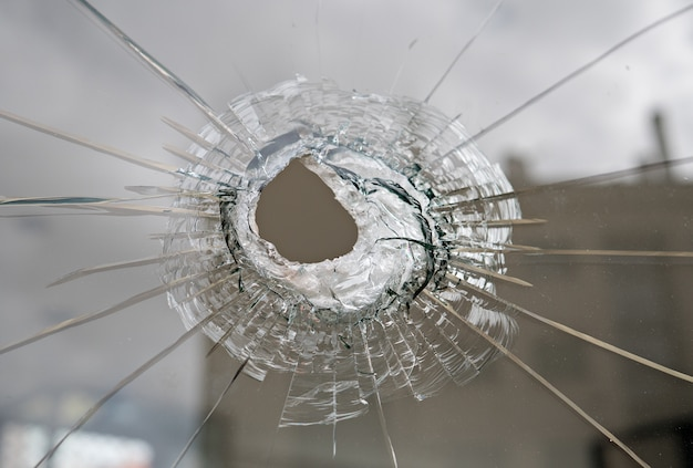 Vandalisme of geweldconcept. gebroken glas met gat