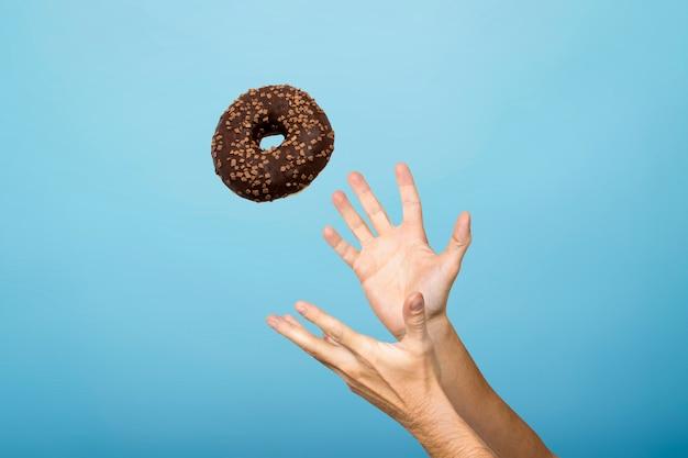 Vang een donut met de hand. concept van het bakken, handgemaakt. plat lag, bovenaanzicht