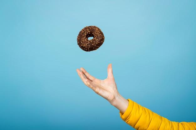 Vang een doughnut met chocoladesuikerglazuur met de hand. blauwe kartonnen achtergrond. concept van het bakken, handgemaakt. plat lag, bovenaanzicht