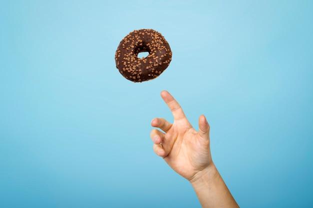 Vang een doughnut met chocoladesuikerglazuur met de hand. concept van het bakken, handgemaakt. plat lag, bovenaanzicht