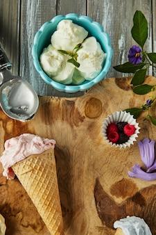 Vanille-, bosbessen- en frambozenijs in wafelkegels en ijs in beker op houten bord met bessen en bloemen.