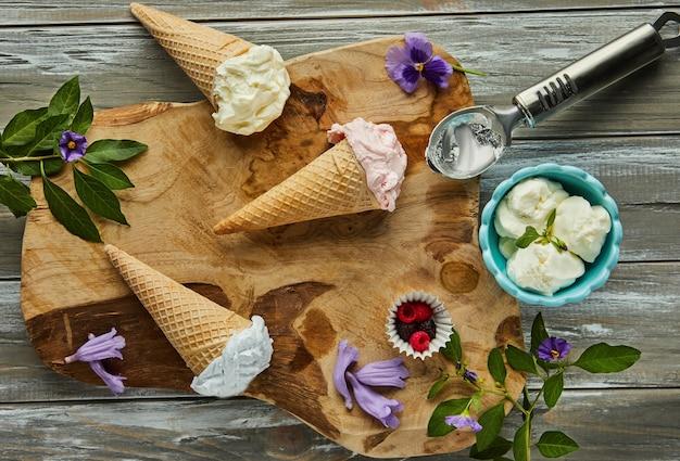 Vanille-, bosbessen- en frambozenroomijs in wafelkegels op een houten bord met bessen en bloemen. plat leggen.