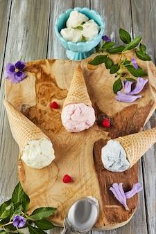Vanille-, bosbessen- en frambozenroomijs in wafelkegels op een houten bord met bessen en bloemen.
