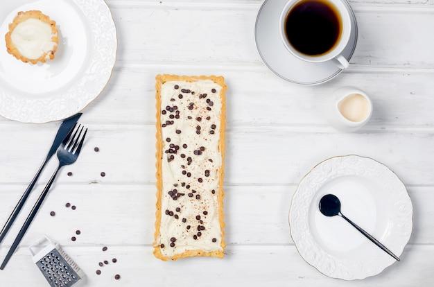 Vanille crème taart met chocolade druppels en kopje koffie op witte houten achtergrond