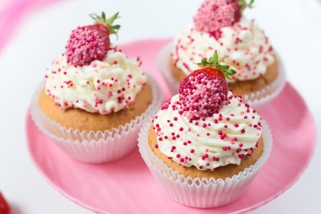 Vanille cupcakes ingericht aardbeien op roze taart staan