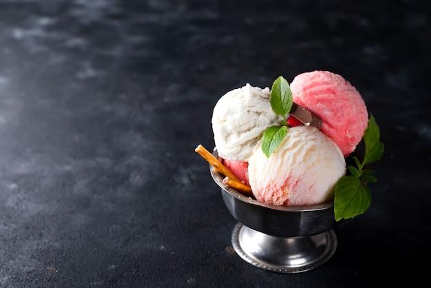 Vanille en roze ijs in een kom met bevroren bessen en wafelkegel