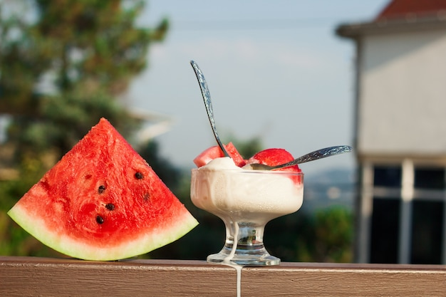 Vanille-ijs geserveerd met watermeloenschijfjes, koud zomerdessert op het terras
