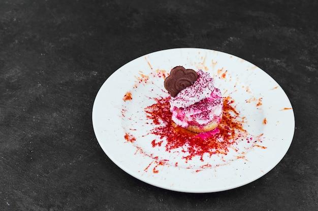 Vanille-ijs met aardbeiensiroop en chocolade in een witte plaat.