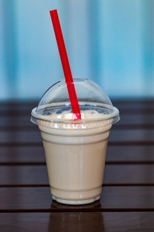 Vanille milkshake bedekt met slagroom in plastic glas op houten ondergrond.