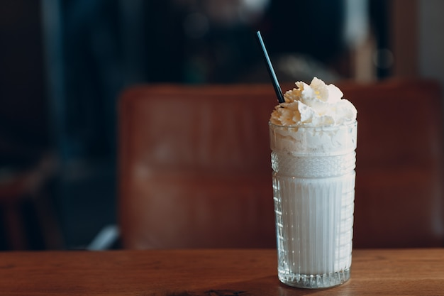 Vanille milkshake met een rietje in een glazen beker op tafel