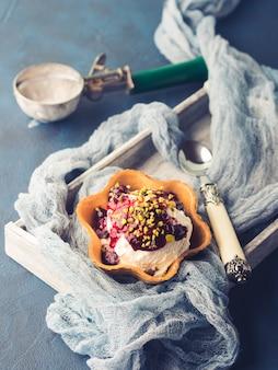 Vanille zelfgemaakte ijs scoops in wafel cup met bessensaus en pistachenoten. zoete traktatie