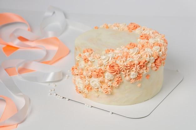 Vanillecake met crèmekleurige bloemendecoratie en linten.