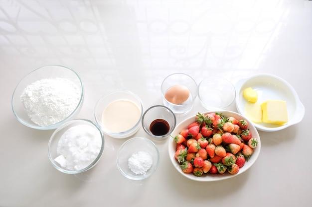 Vanillemeel, boter, melk, suiker, eieren en aardbeien als grondstoffen voor het bakken