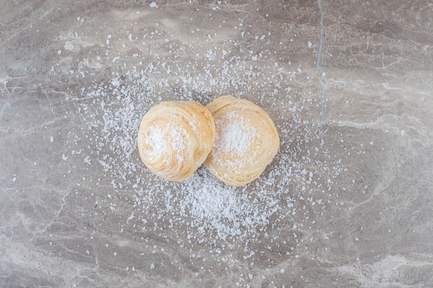 Vanillepoeder en twee schilferige koekjes op marmeren oppervlak