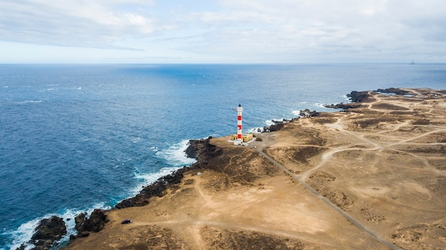 Vanuit de lucht oogpunt van vuurtoren aan de kust om licht te maken op de oceaan voor schepen. veel wegen om overal naartoe te gaan en plekken in de woestijn te ontdekken. reis avontuur concept