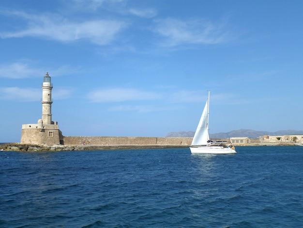 Varend wit jacht dichtbij de vuurtoren op het blauwe egeïsche overzees, het eiland van kreta, griekenland
