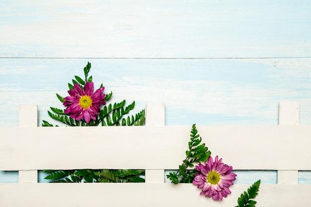 Varens en bloemen achter witte hek