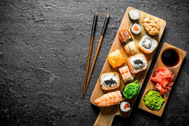 Varianten van soorten sushi, broodjes en maki op een snijplank met stokken.
