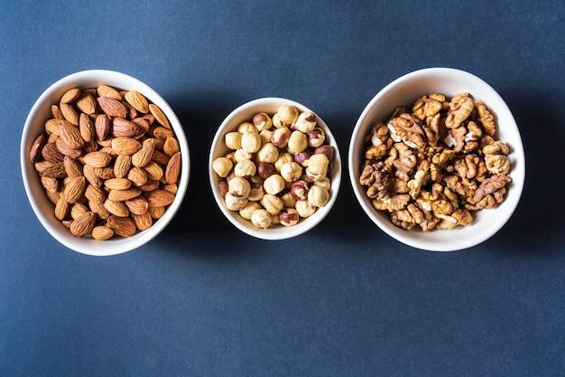 Variatie van noten in kommen op grijze achtergrond.