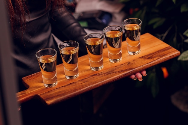 Variatie van sterke alcoholische shots geserveerd op toog. vervaag flessen op de achtergrond.