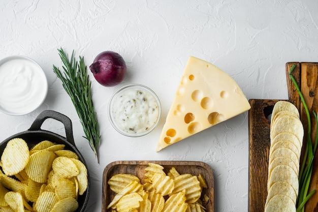 Variatie verschillende aardappelchips set met kaas en ui, met dipsauzen tomaat dip zure room, op witte stenen ondergrond, bovenaanzicht plat leggen