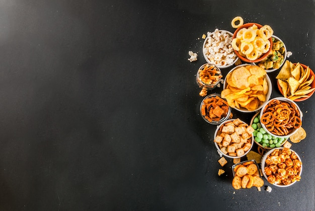 Variatie verschillende ongezonde snacks crackers zoete gezouten popcorn tortilla's noten rietjes bordjes terug schoolbord
