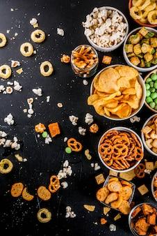 Variatie verschillende ongezonde snacks crackers, zoete gezouten popcorn, tortilla's, noten, rietjes, bretsels