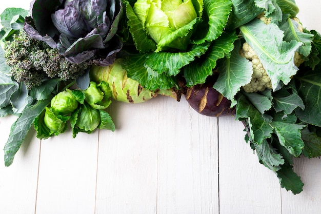 Varioassorted of cabbages on white wooden surface,