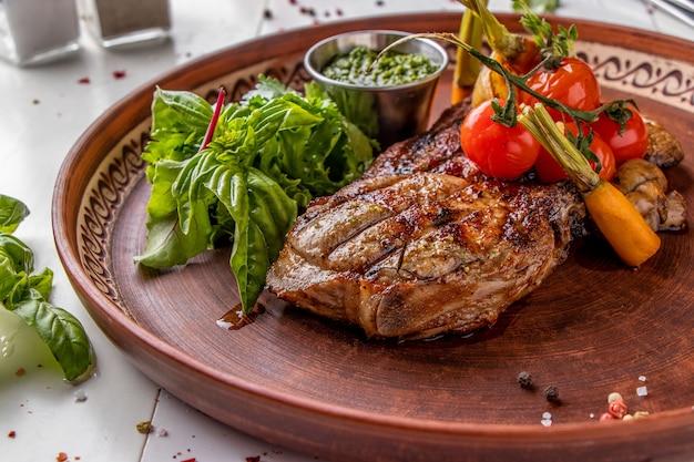Varkensbiefstuk geserveerd met gegrilde groenten, champignons en pestosaus