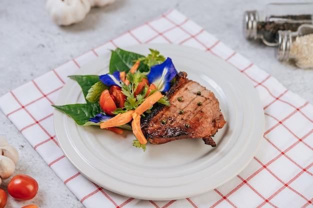 Varkensbiefstuk met tomaat, wortel, rode ui, pepermunt, vlindererwtenbloem en limoen.