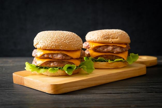 Varkenshamburger of varkensburger met kaas op houten plank