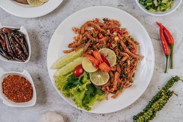 Varkenshuid larb met wortel, komkommer, limoen, bosui, chili, versgemalen peper en sla.