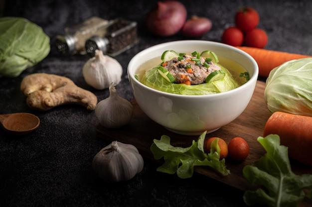 Varkenskoolsoep met wortelen, gehakte groene uien, komkommer in een houten plaat op een houten plaat
