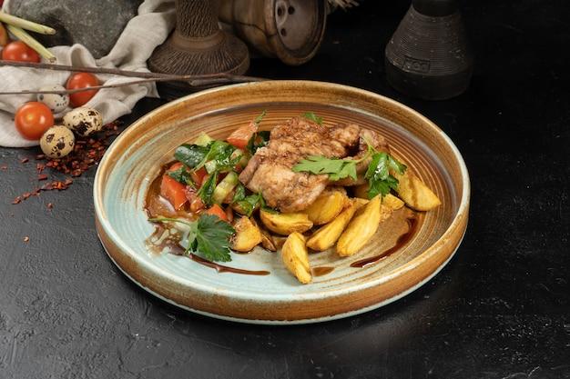 Varkenskotelet met gebakken aardappelschijfjes en groentesalade van tomaten en komkommers and