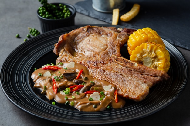 Varkenskoteletlapje vlees met champignonsaus en frietendeeg op een zwarte achtergrond.