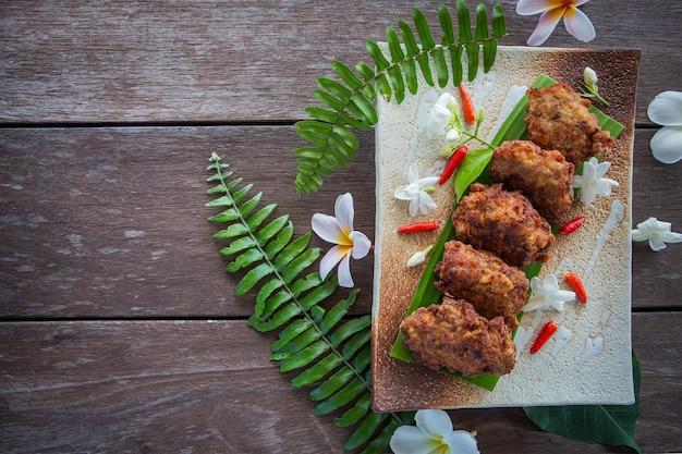 Varkenskoteletten ballen gebakken op een bord met bladeren rond geplaatst op een houten achtergrond