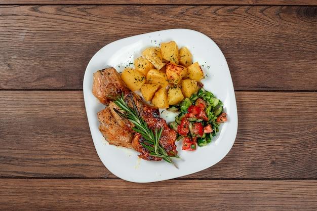 Varkenslapje vlees, gebakken aardappelen, salade en een takje rozemarijn.