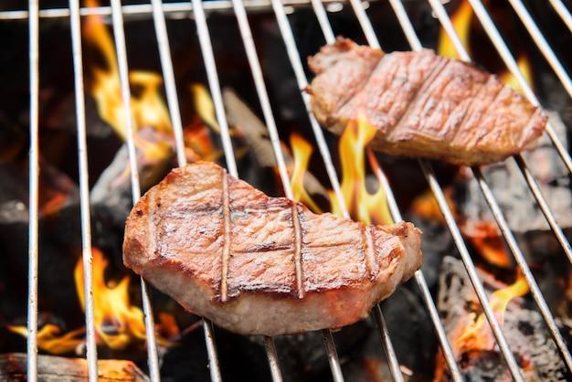 Varkenslapje vlees koken over vlammende grill.