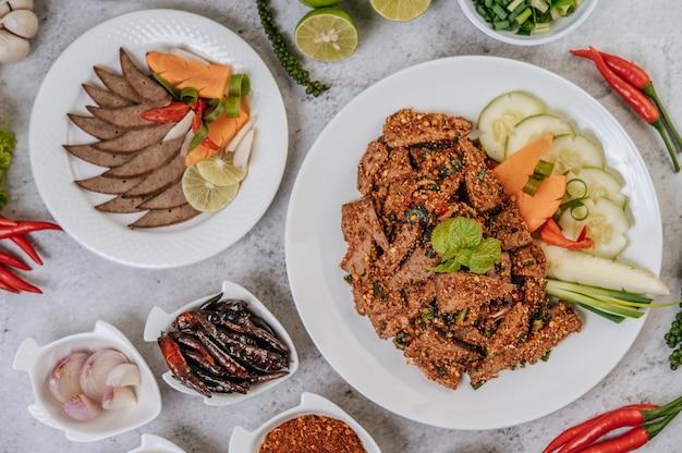 Varkensleversalade met chili, geroosterde rijst, bosui, wortel en komkommer.