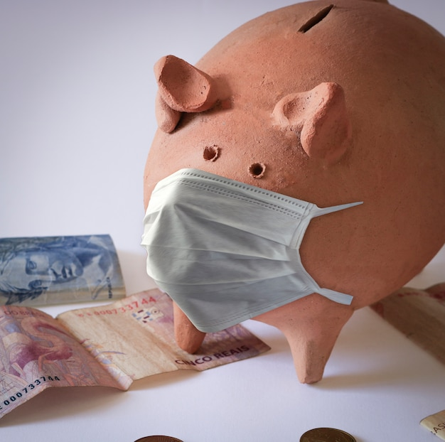 Varkensmunt met masker en braziliaanse bankbiljetten en munten