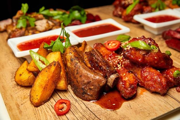 Varkensribbetjes met gebakken aardappelen en tomatensaus