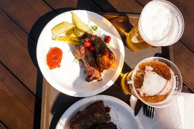 Varkensribbetjes op een dienblad en licht bier streetfood festivalvoedsel op een zonnige dag