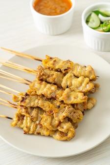 Varkenssaté met augurken in pindasaus, plakjes komkommer en uien in azijn - aziatische stijl