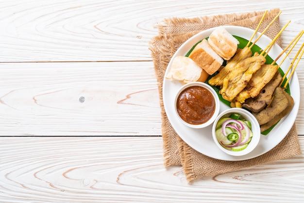 Varkenssaté met uw pindasaus en augurken die plakjes komkommer zijn en uien in azijn